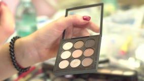 采取从多色构成眼影膏调色板的化妆师眼影在美容院 五颜六色的专家se特写镜头  免版税库存照片