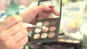 采取从多色构成眼影膏调色板的化妆师眼影在美容院 五颜六色的专家se特写镜头  库存图片
