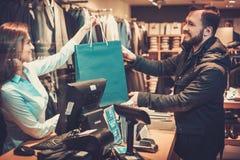 采取从女推销员的愉快的英俊的人购物袋在衣服商店 库存照片