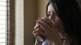 采取从她的咖啡杯的年轻美丽的妇女画象饮者 影视素材