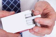 采取从小包的人手香烟 库存照片