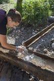采取从山小河的年轻俏丽的妇女水 免版税库存照片