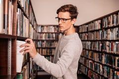 采取从架子的大学生一本书在图书馆里 免版税库存照片