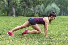 采取锻炼的少妇在公园 免版税库存图片