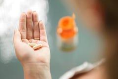 采取维生素人参钙药片的少妇 免版税图库摄影