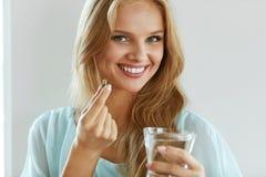 采取维生素药片的美丽的微笑的妇女 饮食补充条款 库存照片