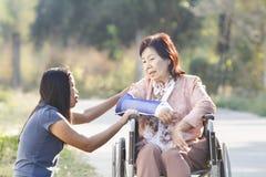 采取他们的母亲的亚裔妇女 免版税库存图片