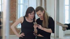 采取从他们的锻炼的一个断裂和与手机的逗人喜爱的愉快的杆舞蹈家社会网络 股票录像