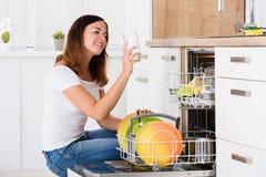 采取从洗碗机的妇女水杯 免版税库存照片