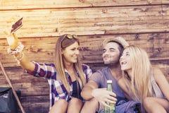 采取滑稽的selfie的小组微笑的朋友 免版税库存图片