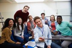 采取画象用Selfie棍子的学生和家庭教师 免版税库存照片