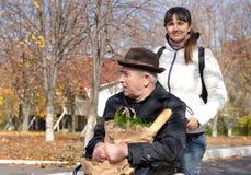 采取年长残疾人购物的妇女 免版税图库摄影