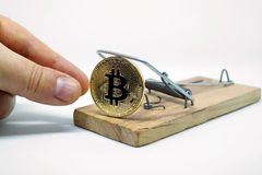 采取bitcoin硬币从捕鼠器的手 库存照片