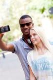 采取foto的年轻人微笑的多种族夫妇由智能手机 免版税图库摄影