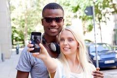 采取foto的年轻人微笑的多种族夫妇由智能手机 库存照片