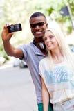 采取foto的年轻人微笑的多种族夫妇由智能手机 免版税库存照片