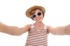 采取selfie与手机的年轻可爱的女孩照片画象有在别致的时髦旅游神色的夏天礼服的 免版税库存图片