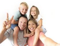 采取selfie与手机运载的儿子和女儿的可爱的年轻夫妇照片自画象摆在愉快的smilin的肩膀的 免版税库存照片