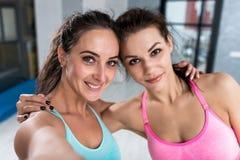 采取selfie佩带的体育胸罩的两个女孩户内 特写镜头微笑对照相机的射击了女运动员拥抱其中每一 图库摄影