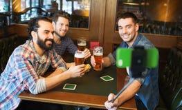 采取selfie和喝啤酒的朋友在酒吧 库存照片