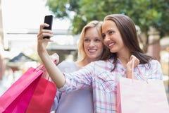 采取selfie和拿着购物袋的愉快的妇女朋友 免版税库存照片