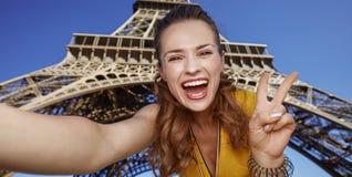 采取selfie和显示胜利的妇女反对埃佛尔铁塔 免版税图库摄影