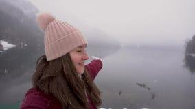 采取selfie和显示Ritsa湖的愉快的旅行家妇女在阿布哈兹在冬天 股票录像