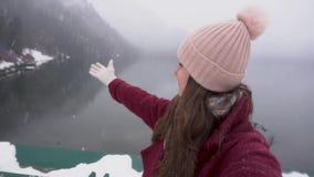 采取selfie和显示Ritsa湖的愉快的旅行家妇女在阿布哈兹 斯诺伊天在冬天 股票视频