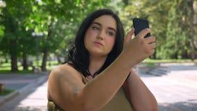采取selfie和身分在街道上的迷人的年轻超重妇女在公园,美好的晴朗的天气户外 影视素材