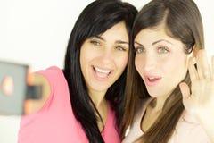 采取selfie微笑,友谊的两年轻女人 免版税库存图片