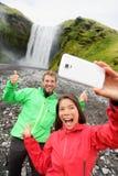 采取selfie智能手机图片瀑布的夫妇 免版税库存照片