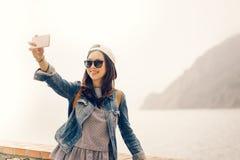 采取selfie有海景背景,软的温暖的轻的口气的美丽的亚裔旅客 免版税图库摄影