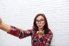 采取Selfie照片吹的亲吻嘴唇聪明的电话照相机的女孩 库存图片