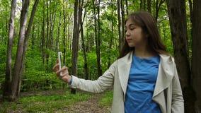 采取selfie照片智能手机的女孩在公园在夏天 摆在和微笑 录影射击静止照相机 股票视频