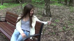 采取selfie照片智能手机, loseup的女孩采取在公园在夏天 摆在和微笑 录影射击行动照相机 股票录像