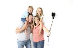 采取selfie照片自画象用棍子和手机运载的儿子和女儿的可爱的年轻夫妇摆在ha的肩膀的 免版税库存图片