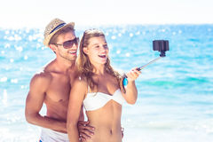 采取selfie用selfie棍子的愉快的夫妇 免版税库存图片