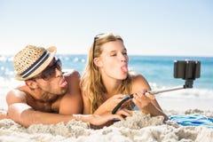 采取selfie用selfie棍子的愉快的夫妇 免版税库存照片