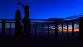 采取selfie画象摄影师的一对爱恋的夫妇的剪影在五颜六色的日落天空背景下 库存照片