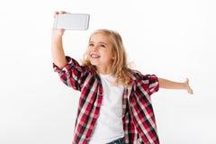 采取selfie的一个激动的小女孩的画象 免版税库存照片