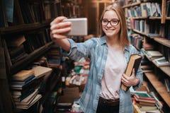 采取selfie的一个白肤金发的女孩的一张逗人喜爱的图片 她看对电话和微笑 这女孩是在大公众 库存图片