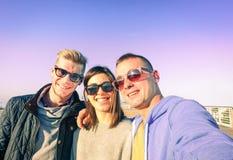 采取selfie的三个年轻朋友在晴朗的秋天天 库存图片