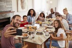 采取Selfie的两个家庭,他们一起在家享受膳食 库存照片