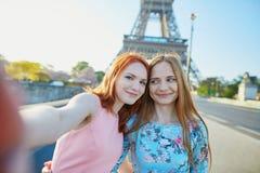 采取selfie的两个朋友在埃佛尔铁塔附近在巴黎,法国 库存照片