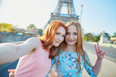 采取selfie的两个朋友在埃佛尔铁塔附近在巴黎,法国 库存图片