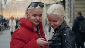 采取selfie的两个滑稽的朋友户外在街道在与温暖的光的日落在背景中,女孩姐妹与 影视素材