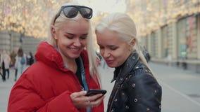 采取selfie的两个滑稽的朋友户外在街道在与温暖的光的日落在背景中,女孩姐妹与 股票录像