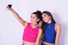 采取selfie的两名时髦的妇女 湿背景概念黑暗的友谊鹈鹕的纵向二 库存图片