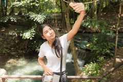 采取selfie的亚裔妇女在森林里 库存图片