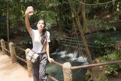 采取selfie的亚裔妇女在森林里 免版税图库摄影